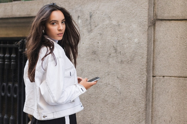 Jeune femme en veste regardant par-dessus l'épaule tenant le téléphone portable à la main Photo gratuit