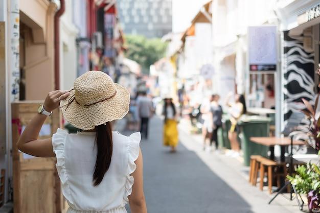 Jeune femme voyageant avec une robe blanche et un chapeau Photo Premium