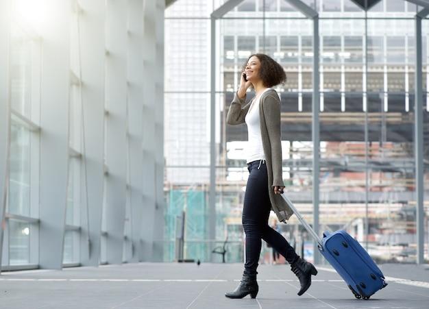 Jeune femme voyageant avec téléphone portable et valise Photo Premium