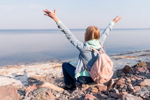 Jeune femme voyageur assis sur la plage en levant les bras surplombant la mer Photo gratuit