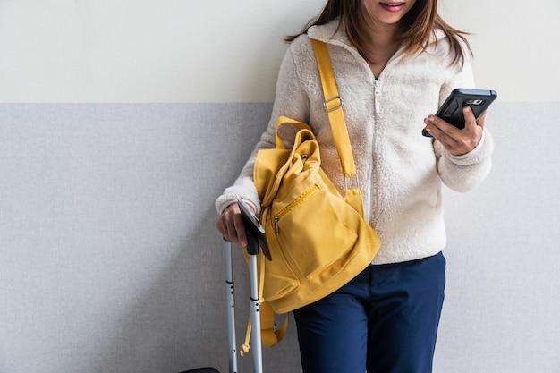 Jeune femme voyageur avec bagages et sac à dos à l'aide de smartphone à l'aéroport Photo Premium