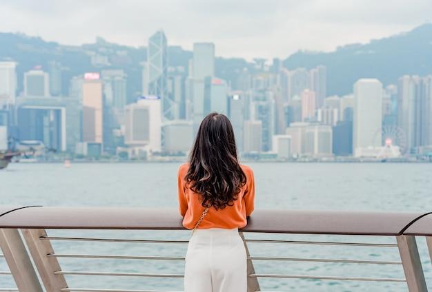 Jeune femme voyageur profitant au centre-ville de hong kong au centre-ville sur le port de victoria Photo Premium