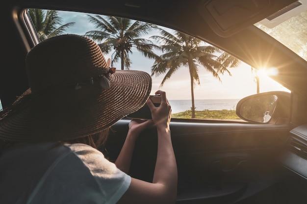 Jeune femme voyageur à la recherche et prendre une photo beau coucher de soleil à la plage à l'intérieur de la voiture Photo Premium