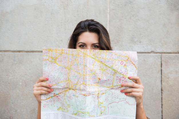 Jeune femme voyageur regardant par derrière la carte Photo gratuit
