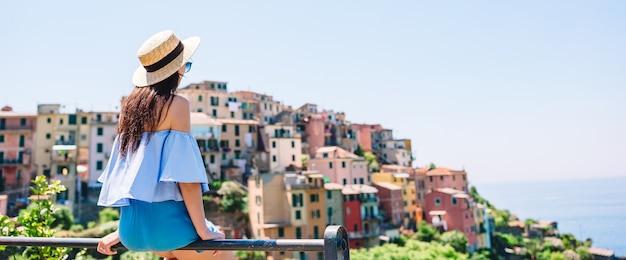 Jeune femme avec une vue magnifique sur le vieux village de cinque terre, ligurie, italie. Photo Premium