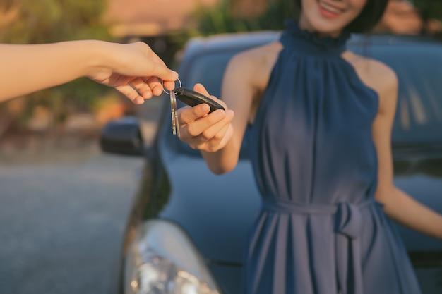 Jeune fille adulte reçoit la télécommande par clé intelligente de sa nouvelle voiture Photo Premium