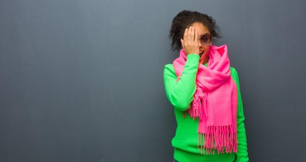 Jeune fille afro-américaine aux yeux bleus criant heureux et couvrant le visage avec la main Photo Premium