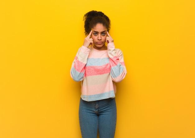 Jeune fille afro-américaine noire aux yeux bleus faisant un geste de concentration Photo Premium