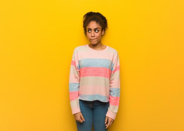 Jeune fille afro-américaine noire aux yeux bleus pense à une idée Photo Premium