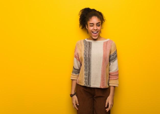 Jeune fille afro-américaine noire avec des yeux bleus un clin de œil, geste drôle, sympathique et sans soucis Photo Premium