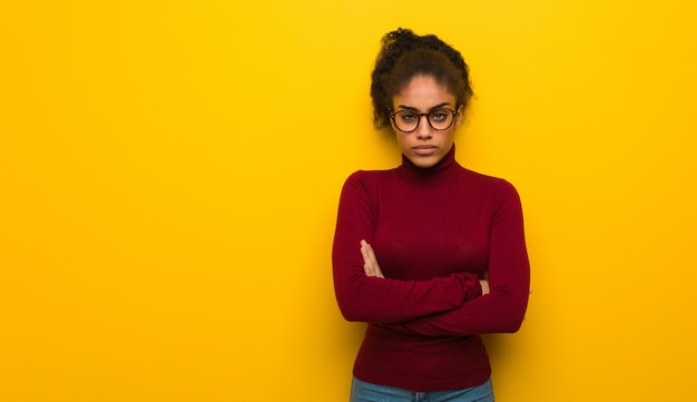 Jeune fille afro-américaine noire avec des yeux bleus croisant les bras détendue Photo Premium