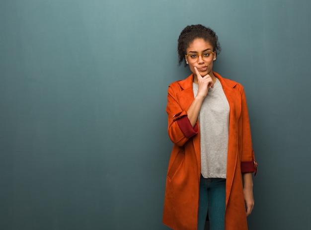 Jeune fille afro-américaine noire avec des yeux bleus doutant et confus Photo Premium