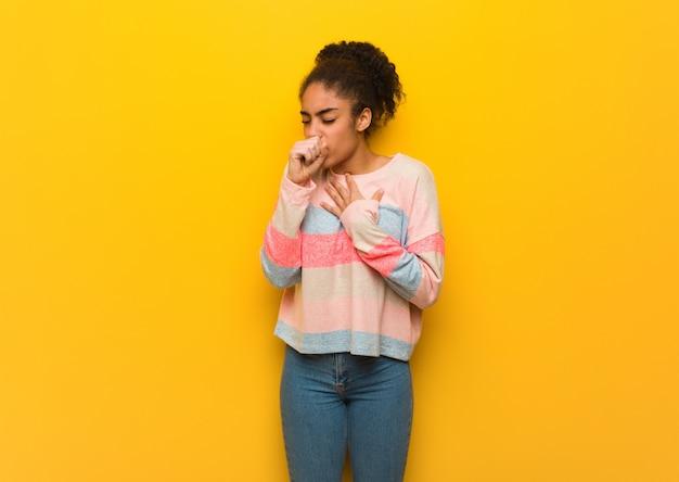 Jeune fille afro-américaine noire avec des yeux bleus toussant, malade en raison d'un virus ou d'une infection Photo Premium