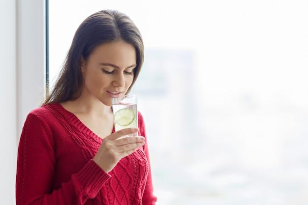 Jeune fille avec un aglass d'eau au citron vert Photo Premium