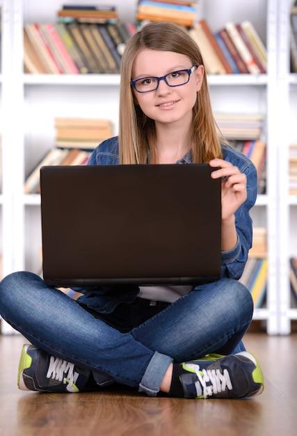 Jeune fille à l'aide d'un ordinateur portable dans la bibliothèque. Photo Premium