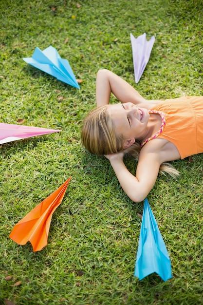 Jeune Fille Allongée Sur L'herbe Autour Des Avions En Papier Photo Premium