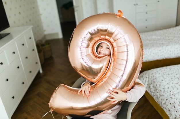 Jeune fille d'anniversaire jolie visage à travers le trou dans le ballon Photo Premium