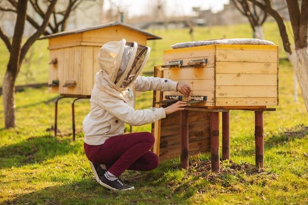Une jeune fille d'apiculteur travaille avec les abeilles et inspecte les ruches après l'hiver Photo Premium