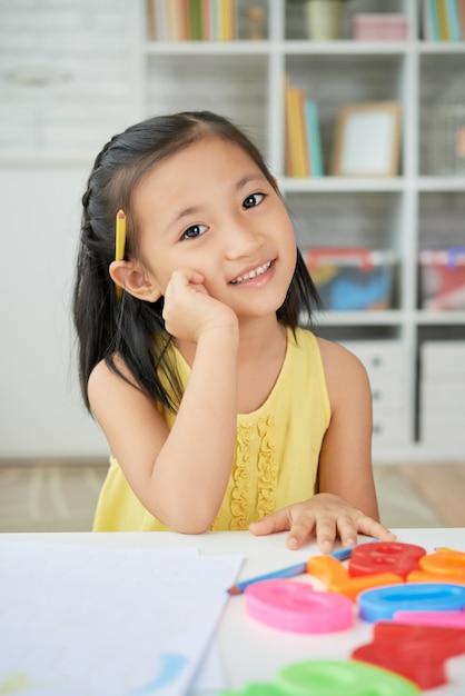 Jeune fille asiatique assise à la maison, avec la main à la joue, un crayon derrière l'oreille et des chiffres en plastique sur le bureau Photo gratuit