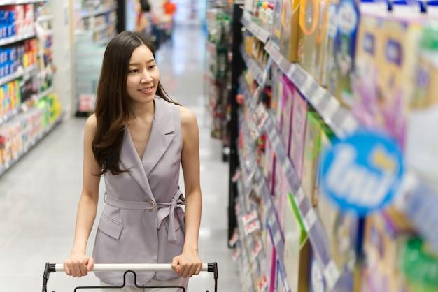 Jeune fille asiatique belle en poussant le panier marchant dans le supermarché. Photo Premium