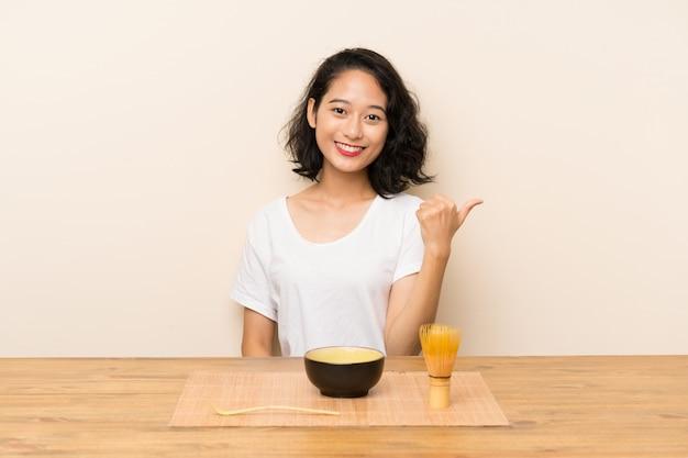 Jeune fille asiatique avec du thé matcha avec le pouce levé parce qu'il s'est passé quelque chose de bien Photo Premium