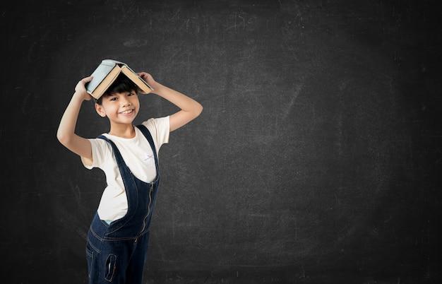 Jeune fille asiatique étudiant tenant livre sur la tête sur fond de tableau Photo Premium