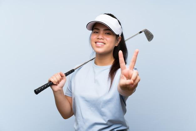 Jeune fille asiatique jeune golfeur sur mur bleu isolé, souriant et montrant le signe de la victoire Photo Premium