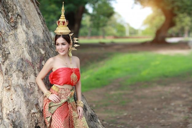 Jeune Fille Asiatique De La Mode En Costume Traditionnel Thaïlandais Debout Avec De Grands Arbres Verts Photo Premium