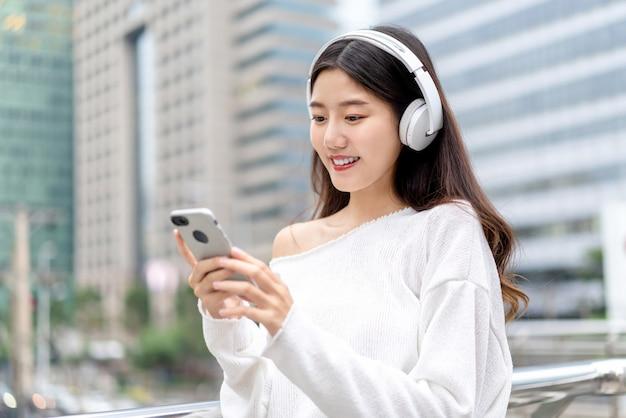 Jeune Fille Asiatique Portant Des écouteurs, écouter De La Musique à Partir D'un Téléphone Mobile Contre Le Bâtiment De La Ville Photo Premium