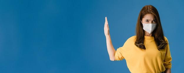 Jeune Fille Asiatique Porter Un Masque Facial Faisant Arrêter De Chanter Avec La Paume De La Main Avec Une Expression Négative Et En Regardant La Caméra. Distanciation Sociale, Mise En Quarantaine Du Virus Corona. Fond Bleu De Bannière Panoramique. Photo gratuit