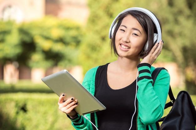 Jeune Fille Asiatique Souriante écoute De La Musique Avec Tablette. Photo Premium