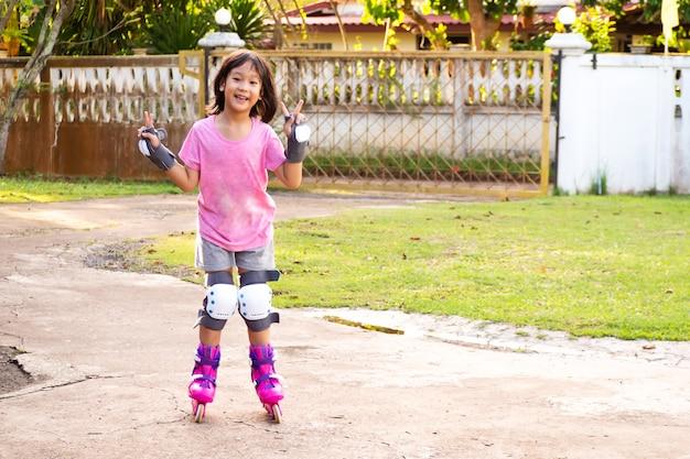 Jeune fille asiatique souriante jouant des patins à roues alignées à la maison. fond de sport de loisirs. Photo Premium