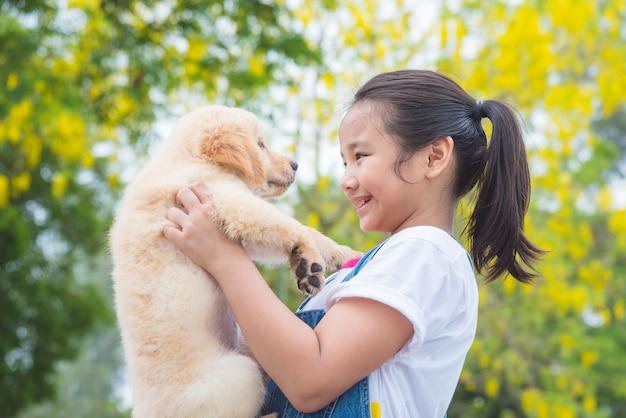 Jeune fille asiatique tenant un petit chien golden retriever dans le parc Photo Premium