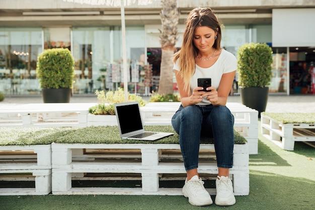 Jeune fille assise avec des appareils portables Photo gratuit