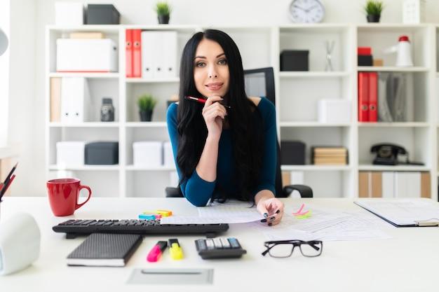 Une jeune fille assise dans le bureau à la table, tient un stylo à la main et remplit les documents. Photo Premium