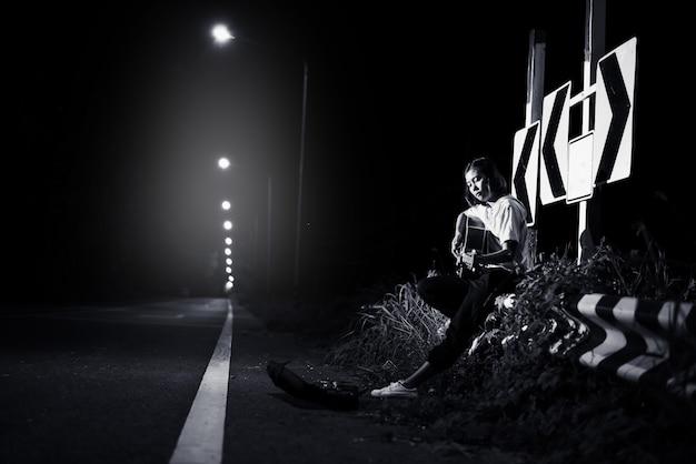 Jeune fille assise et jouant de la guitare au bord de la route avec fond de signe de route, voyage du concept de musicien Photo Premium