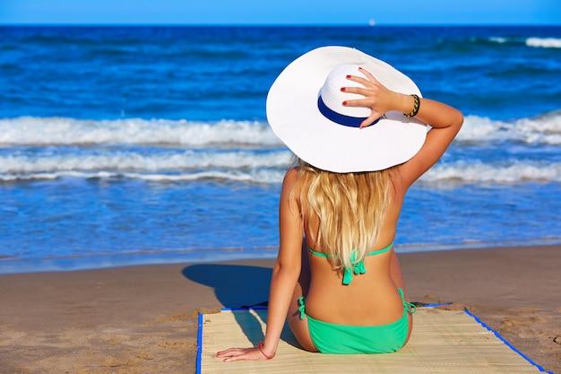 Jeune fille assise en regardant la mer avec un chapeau de plage Photo Premium
