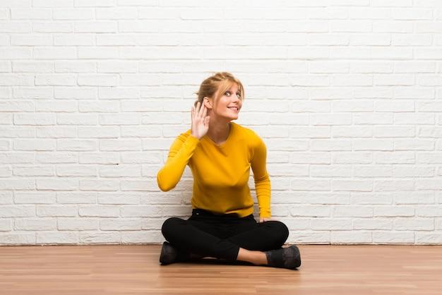 Jeune fille assise sur le sol, écoutant quelque chose en mettant la main sur l'oreille Photo Premium