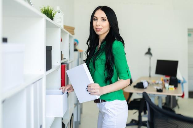 Une Jeune Fille Au Bureau Sort Une Boîte Blanche. Photo Premium