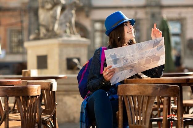 Jeune fille au chapeau bleu se reposant sur la terrasse d'été de la vieille ville et regardant la carte. lviv, ukraine Photo Premium