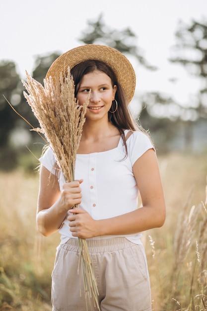 Jeune fille au chapeau dans un champ de blé Photo gratuit