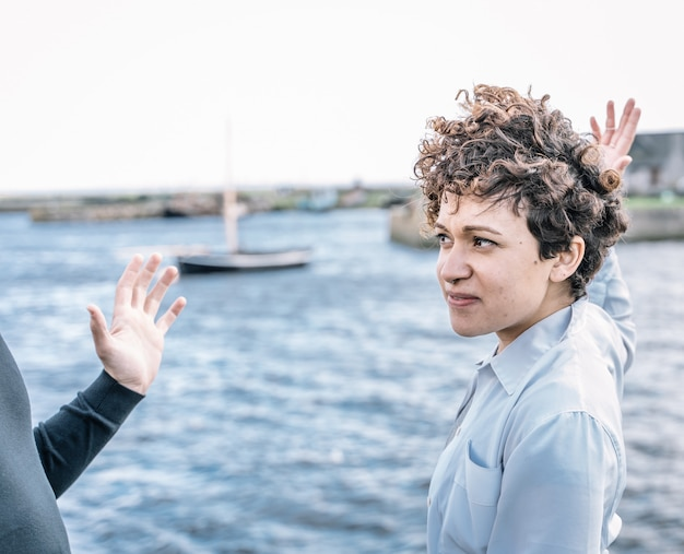 Jeune fille aux cheveux bouclés et au nez perçant se disputant avec son partenaire avec des gestes expressifs avec la mer floue Photo gratuit