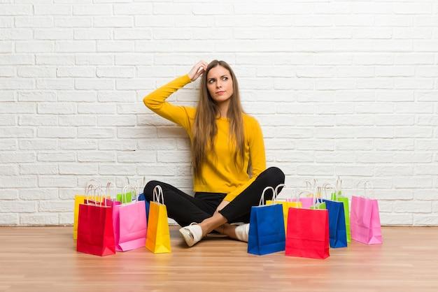 Jeune fille avec beaucoup de sacs à provisions ayant des doutes tout en grattant la tête Photo Premium