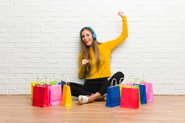 Jeune fille avec beaucoup de sacs à provisions, écouter de la musique avec des écouteurs et danser Photo Premium