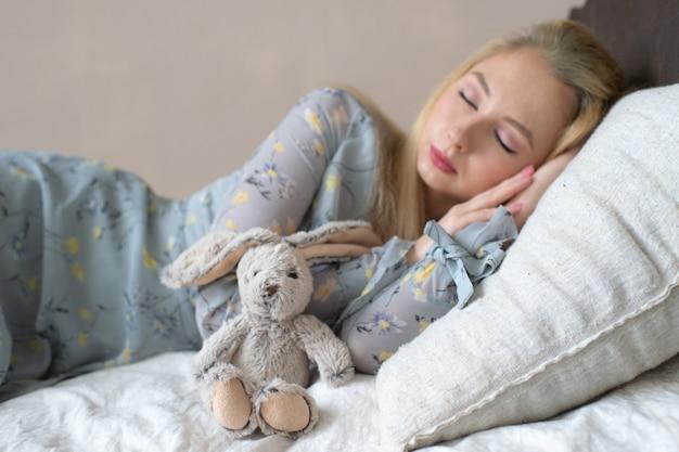 Jeune fille belle, dormant sur le lit avec jouet d'enfant comme enfant Photo Premium