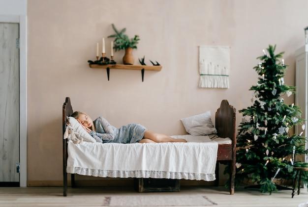 Jeune fille belle, dormant sur le lit avec des jouets comme un enfant dans la chambre avec un arbre de noël. Photo Premium