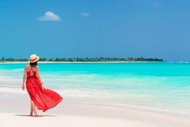 Jeune fille en belle robe rouge à la plage Photo Premium