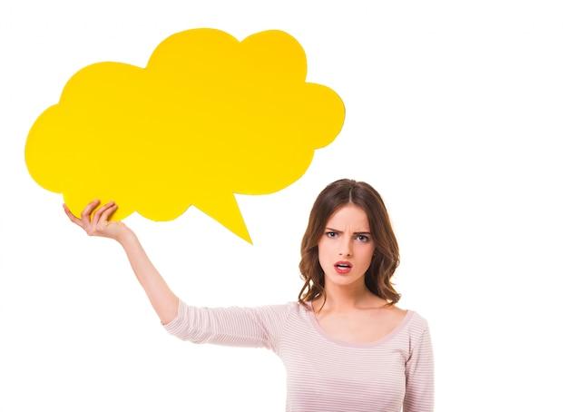 Jeune fille belle, tenant une bulle jaune pour le texte. Photo Premium