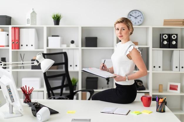 Une jeune fille blonde est assise à son bureau et tient des documents et un crayon. Photo Premium