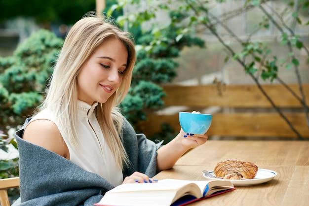 Jeune Fille Blonde Lisant Un Livre En Buvant Du Café Dans Le Salon Du Café En Plein Air. Photo Premium